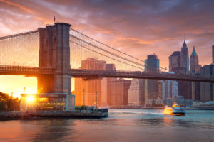 Famous Brooklyn Bridge In New York City With Financial District Downtown Manhattan In Background. Sightseeing Boat On The East River And Beautiful Sunset Over Jane's Carousel.