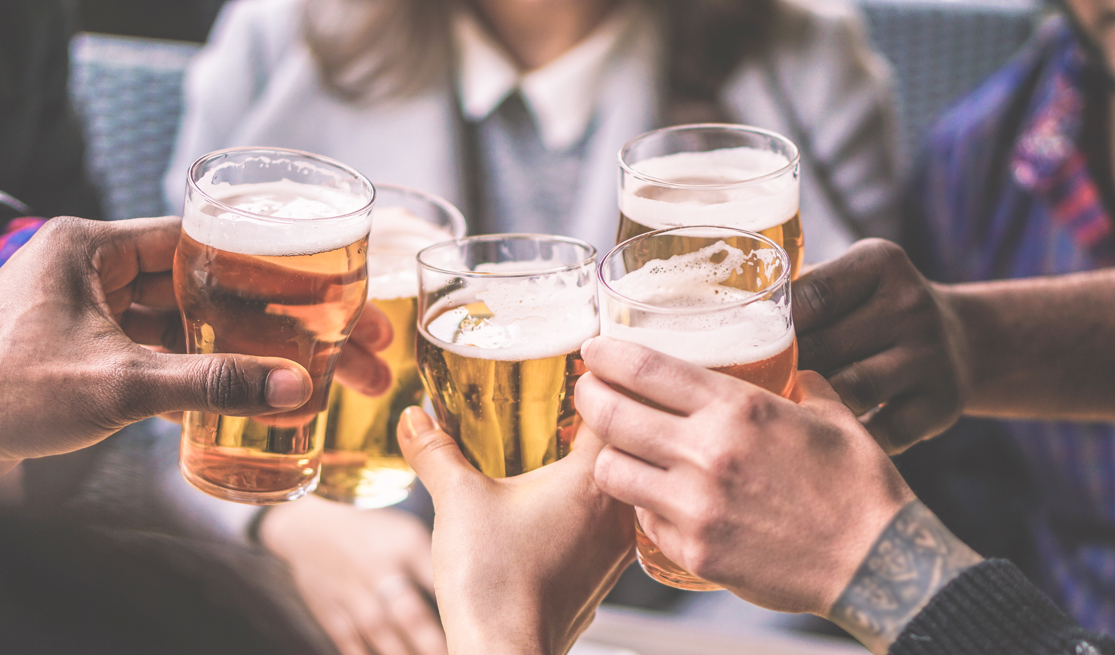 Group Of Friends Enjoying A Beer Glasses In Brewery English Pub Young People Cheering At Bar Restaurant Friendship And Youth Concept Warm Vintage Filter Main Focus On Left Black Hand